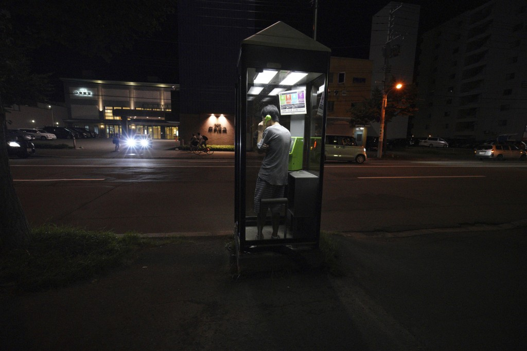 FILE - In this Thursday, Sept. 6, 2018, file photo, a man calls with a public phone in the blackout on the center of Sapporo city, Hokkaido, northern ...