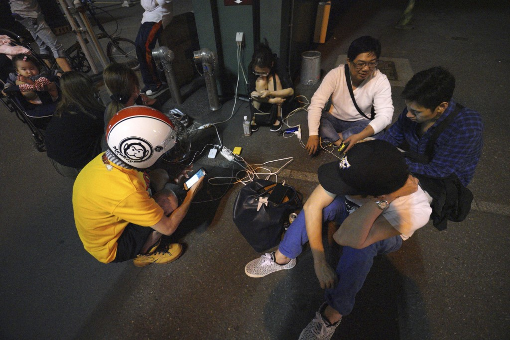 FILE - In this Thursday, Sept. 6, 2018, file photo, people gather to charge their mobile phones in the blackout on the center of Sapporo, Hokkaido, no...