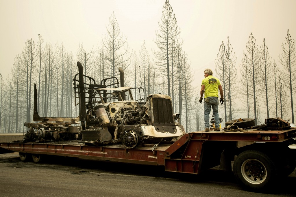Bruce Palmer prepares to tow a truck scorched by the Delta Fire on Interstate 5 in the Shasta-Trinity National Forest, Calif., near Shasta Lake on Thu
