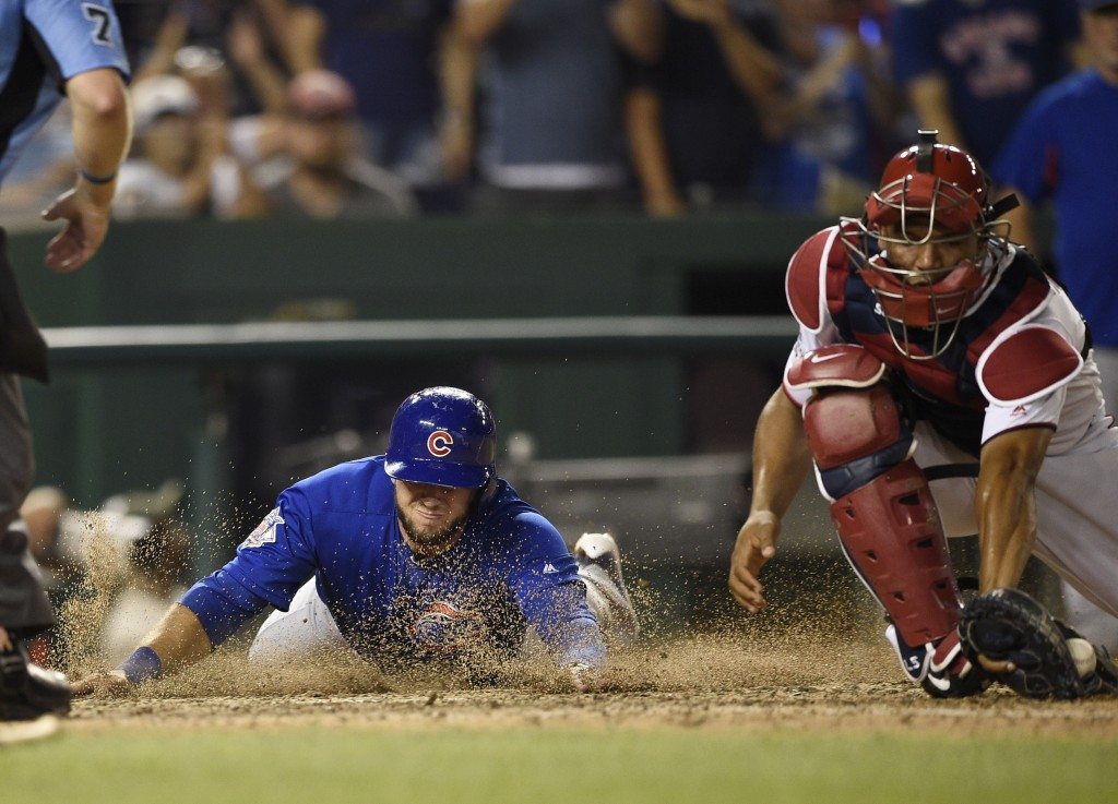 Chicago Cubs' David Bote, left, slides home to score on a single by Taylor Davis against Washington Nationals catcher Pedro Severino during the 10th i...
