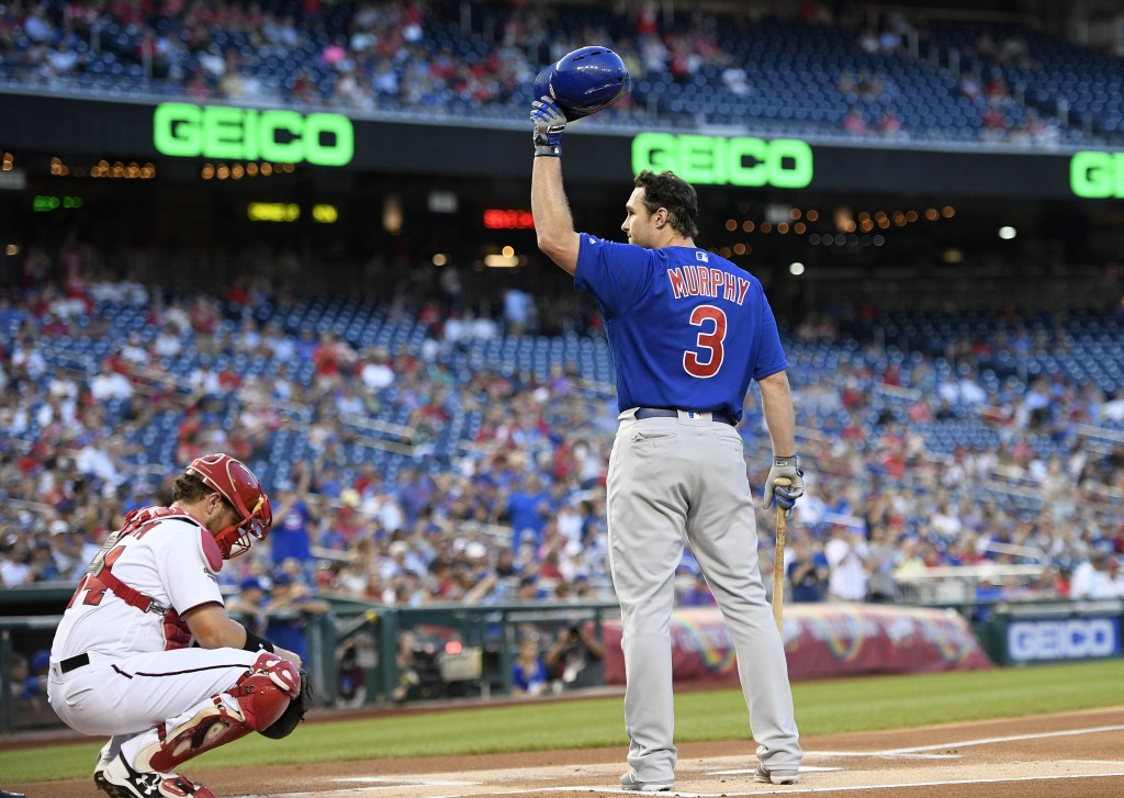 Chicago Cubs' Daniel Murphy waves his batting helmet to the crowd before his at-bat to start a baseball game against the Washington Nationals, Thursda