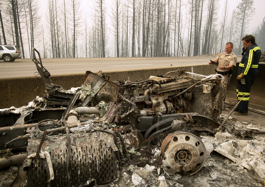 California Capt. Mark Loveless examines a scorched license plate on Interstate 5 as the Delta Fire burns in the Shasta-Trinity National Forest, Calif.