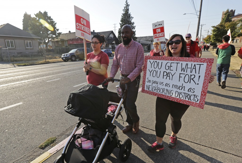 Striking Tacoma Teachers, including Megan Holyoke, left, Nate Bowling, center, and counselor Michelle Ha, right, walk a picket line, Thursday, Sept. 6