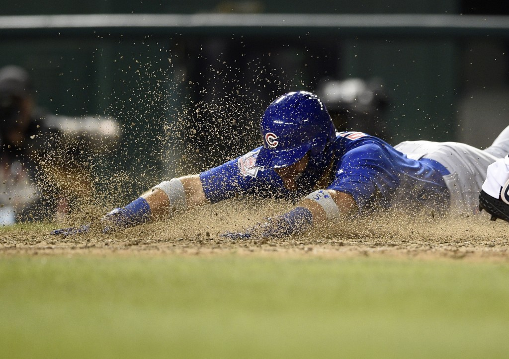 Chicago Cubs' Albert Almora Jr. slides home to score on a double by David Bote during the 10th inning of a baseball game against the Washington Nation...