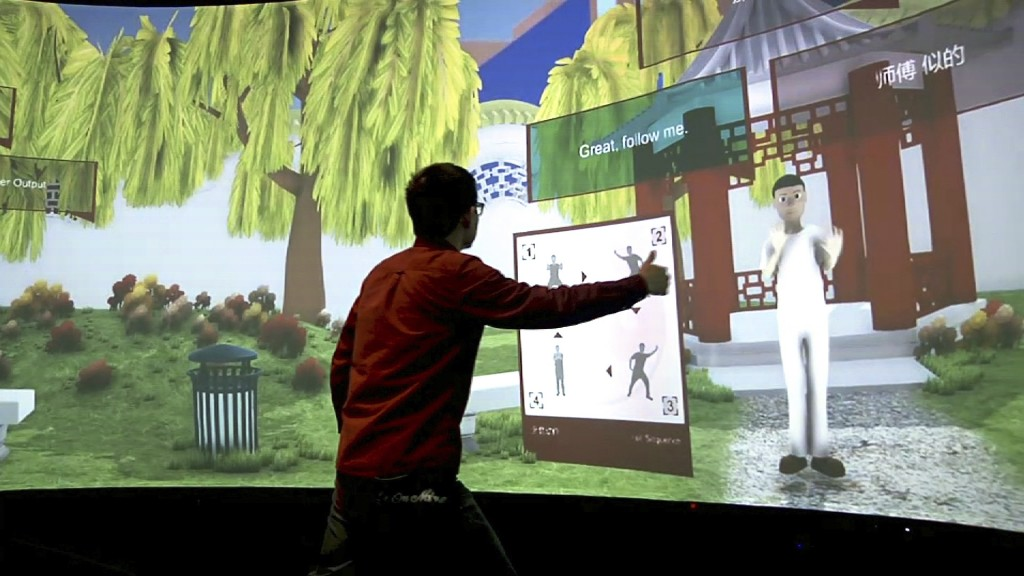 In this Aug. 22, 2018 image taken from video, Rensselaer Polytechnic Institute graduate student Xiangyang Mou practices tai chi with an avatar in a ca...