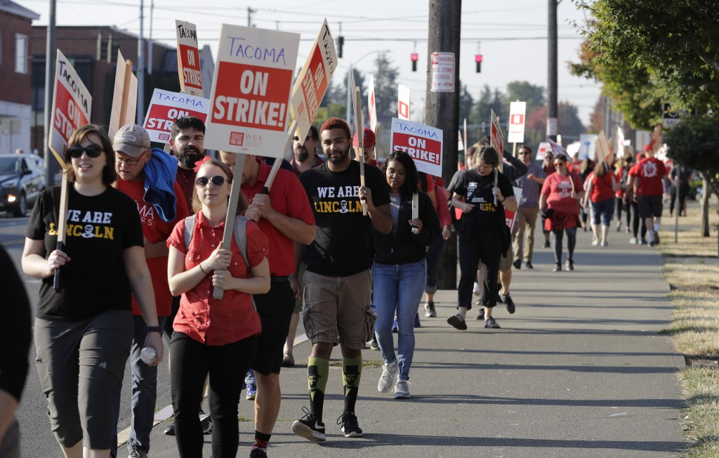 Striking Tacoma Teachers walk a picket line, Thursday, Sept. 6, 2018, in front of Lincoln High School in Tacoma, Wash. Fights over teacher salaries an