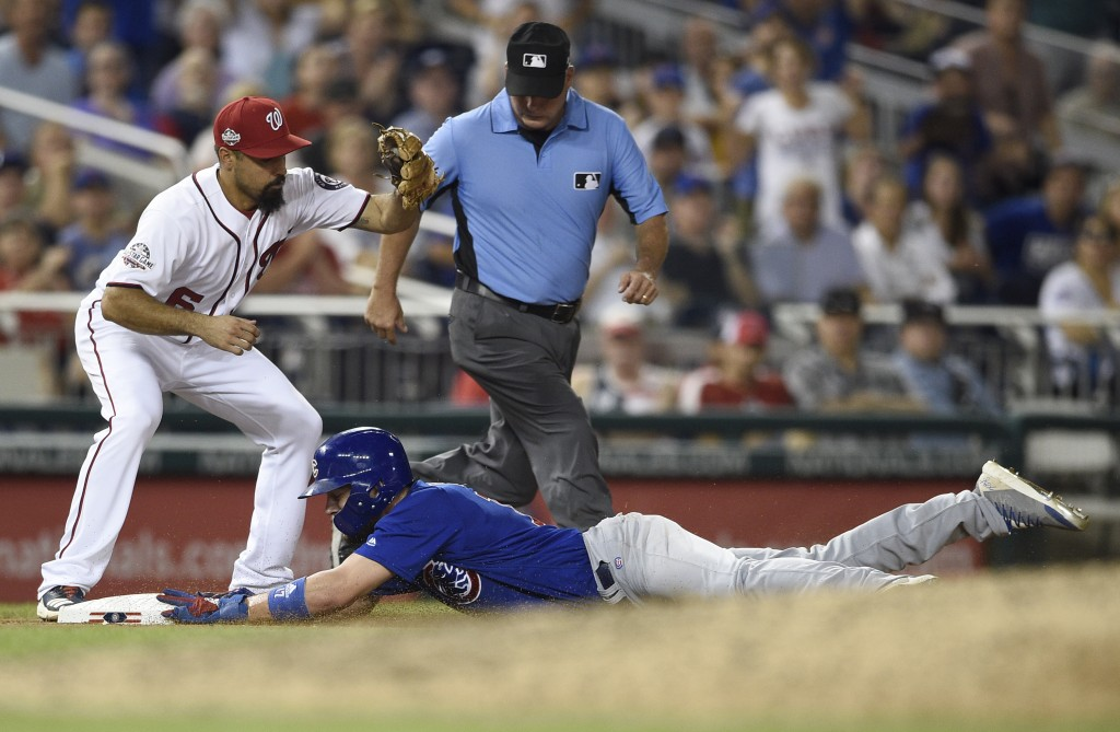 Chicago Cubs' Kris Bryant, bottom, slides safely into third on a single by Albert Almora Jr., next to Washington Nationals third baseman Anthony Rendo...