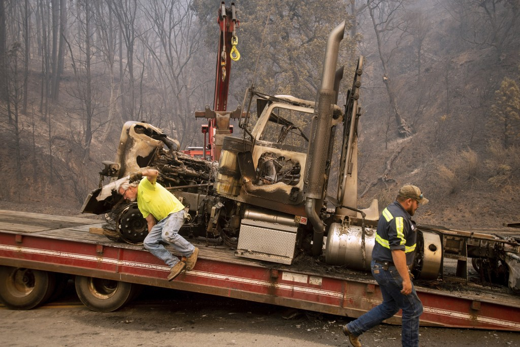 Bruce Palmer, left, and Justice Geib prepare to tow a truck scorched by the Delta Fire on Interstate 5 in the Shasta-Trinity National Forest, Calif.,