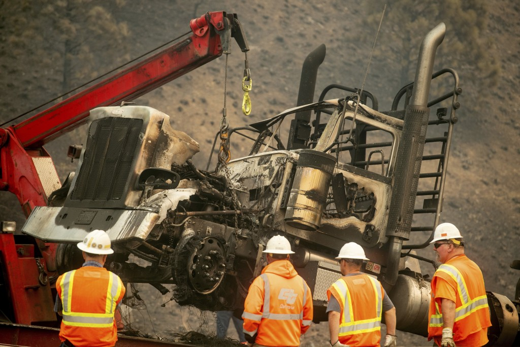 A crane lifts a truck scorched by the Delta Fire on Interstate 5 in the Shasta-Trinity National Forest, Calif., on Thursday, Sept. 6, 2018. The highwa