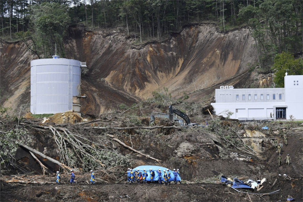 Rescuers carry the body of a victim at the site of a landslide triggered by Thursday's earthquake in Atsuma, Hokkaido, northern Japan Saturday, Sept.