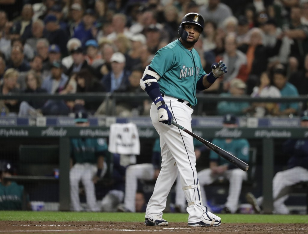Seattle Mariners' Robinson Cano looks toward the infield after he struck out swinging with a man on base to end the sixth inning of a baseball game ag...