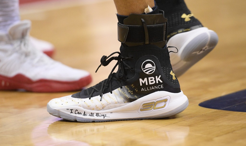 FILE- In this Feb. 28, 2018, file photo Golden State Warriors guard Stephen Curry's shoes are adorned with messages during the first half of the team'...