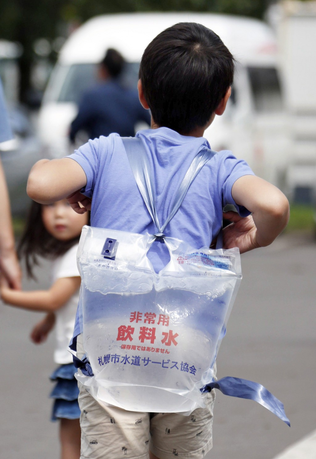 A boy carries a pack of water that he received at a shelter in Atsuma, Hokkaido, northern Japan Saturday, Sept. 8, 2018. The powerful earthquake that