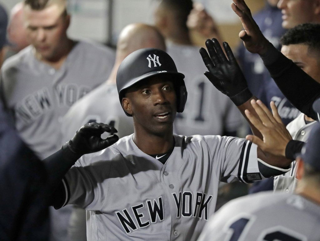 New York Yankees' Andrew McCutchen is greeted in the dugout after he hit a two-run home run during the third inning of a baseball game against the Sea...