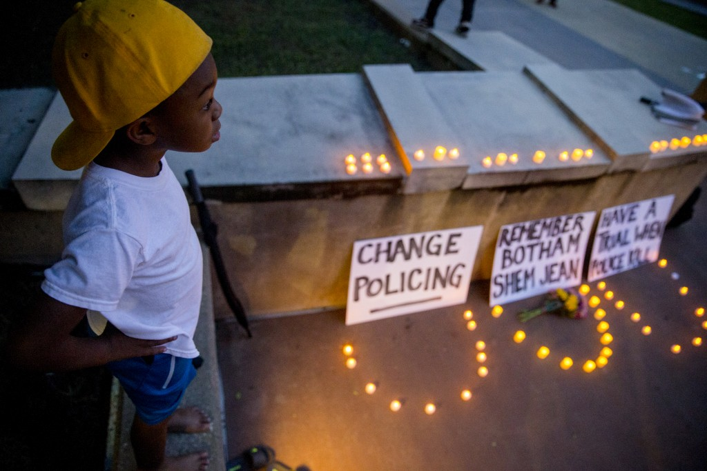 """Young King"" Solomon Grayson, 6, stands on a ledge next to a memorial during a Mothers Against Police Brutality candlelight vigil for Botham Jean at t"