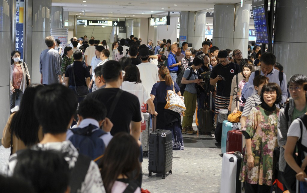 Stranded passengers queue up in lines to wait for their flights at Chitose airport Chitose, Hokkaido, northern Japan, in Saturday, Sept. 8, 2018. The