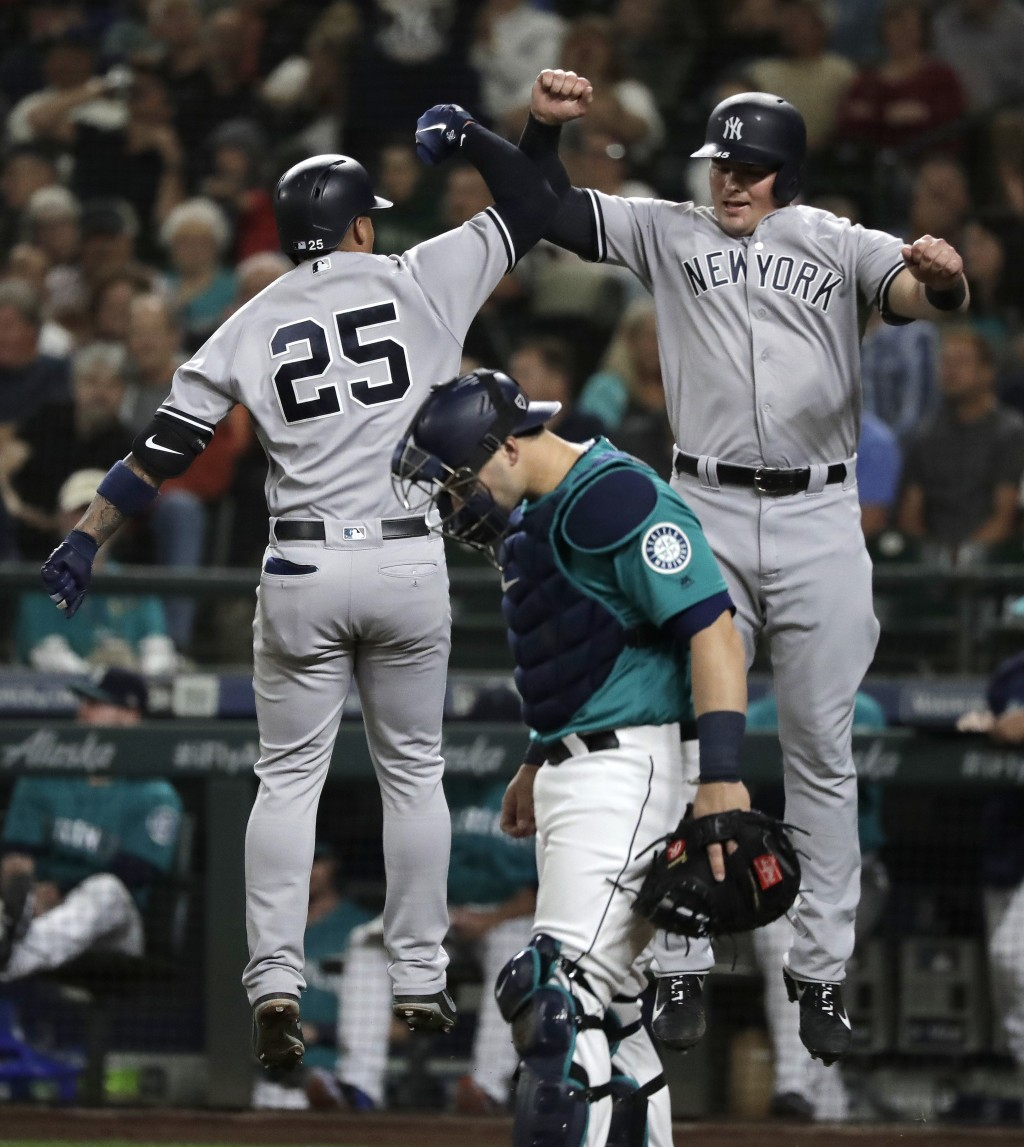 New York Yankees' Gleyber Torres, left, jumps to celebrate with Luke Voit, right, above Seattle Mariners catcher Mike Zunino after Torres hit a two-ru...