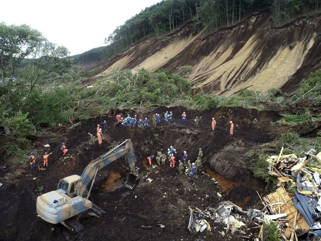 Rescuers search for missing persons at the site of a landslide triggered by Thursday's earthquake in Atsuma, Hokkaido, northern Japan Saturday, Sept.
