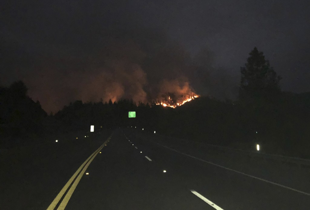 In this photo provided by the California Department of Transportation, lanes are closed on northbound Interstate 5 with the Delta Fire burning in the