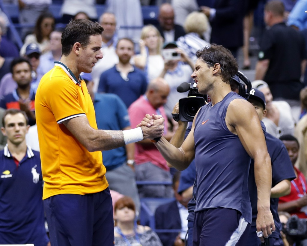 Juan Martin del Potro, of Argentina, shakes hands with Rafael Nadal, of Spain, after Nadal retired from the match during the semifinals of the U.S. Op
