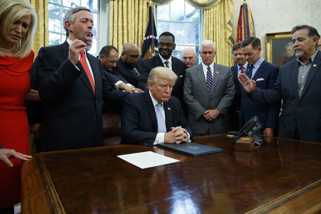 FILE - In this Sept. 1, 2017 file photo, religious leaders pray with President Donald Trump after he signed a proclamation for a national day of praye