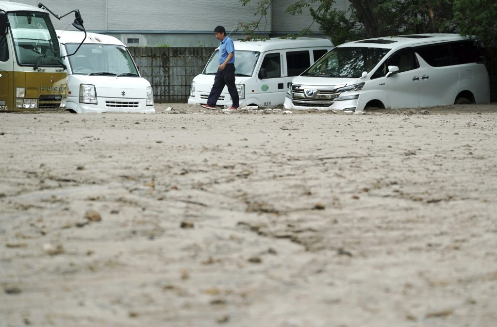 In this Saturday, Sept. 8, 2018, file photo, a worker walks past cars half buried in mud caused by ground liquefaction after a powerful earthquake in