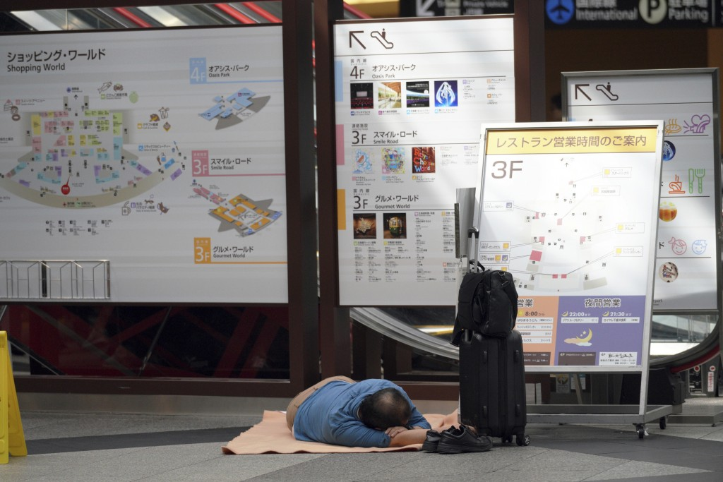 A stranded passenger lies down on the floor as he waits for their flights at Chitose airport in Chitose, Hokkaido, northern Japan, Saturday, Sept. 8,