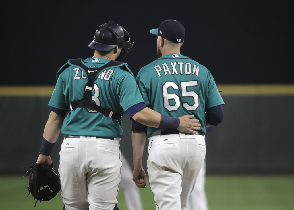 Seattle Mariners starting pitcher James Paxton (65) walks with catcher Mike Zunino at the start of the fifth inning of the team's baseball game agains...