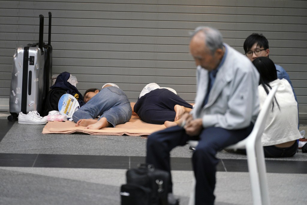 Stranded passengers wait for their flights at Chitose airport in Chitose, Hokkaido, northern Japan, Saturday, Sept. 8, 2018. The regional airport was