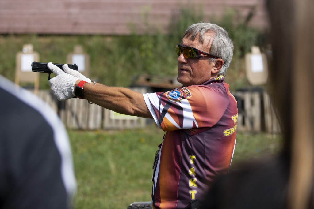 In this photo taken on Sunday, July 29, 2018, shooting instructor Boris Pashchenko demonstrates how to handle a gun at a shooting range in Moscow, Rus