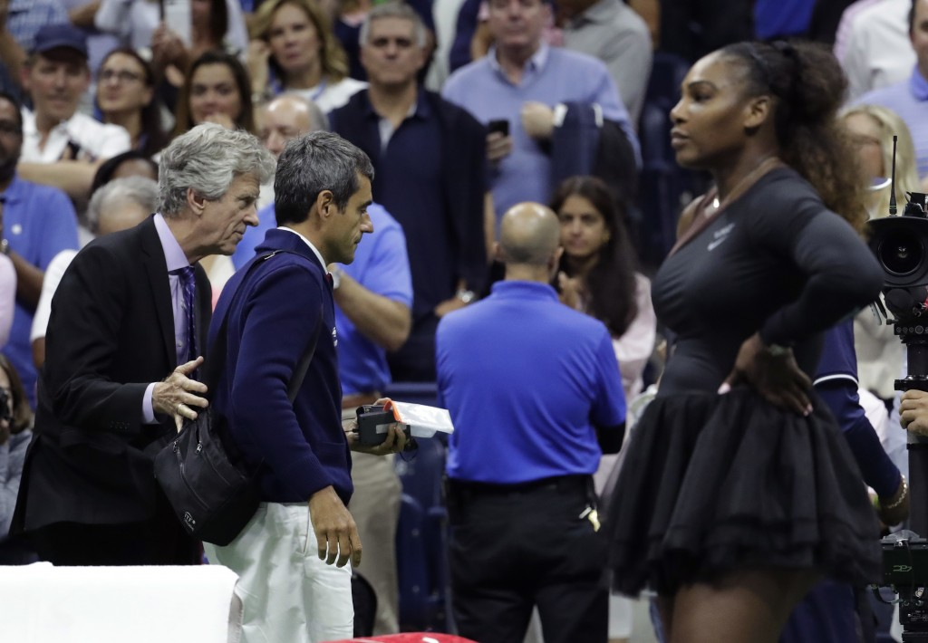 Chair umpire Carlos Ramos, second from left, is lead off the court by referee Brian Earley after Naomi Osaka, of Japan, defeated Serena Williams in th