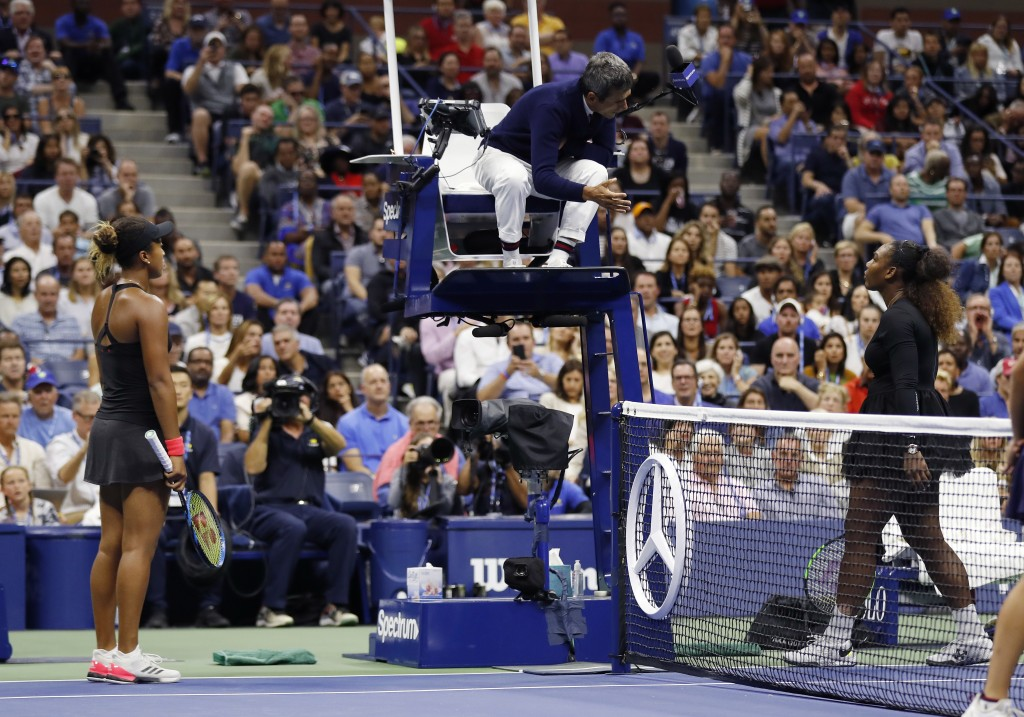 Serena Williams, right, talk with chair umpire Carlos Ramos as Naomi Osaka, of Japan, listens during the women's final of the U.S. Open tennis tournam