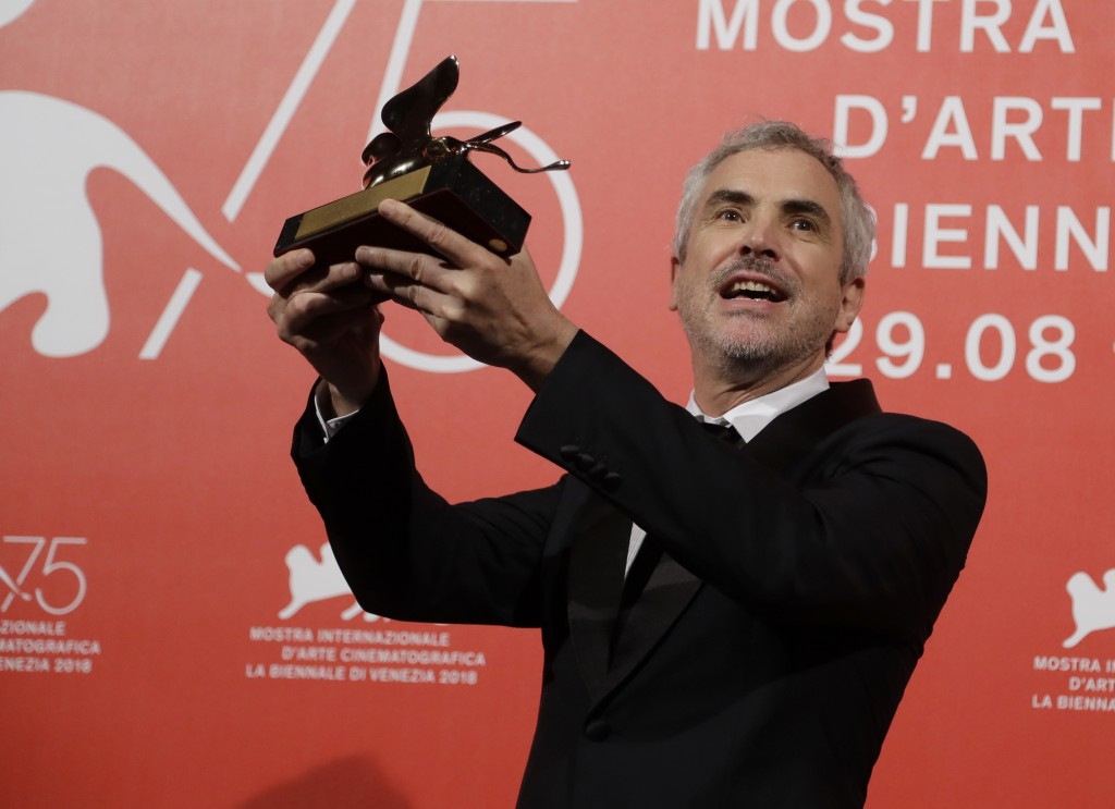 Director Alfonso Cuaron holds aloft the Golden Lion Best Film award for 'Roma' at the awards photo call of the 75th edition of the Venice Film Festiva