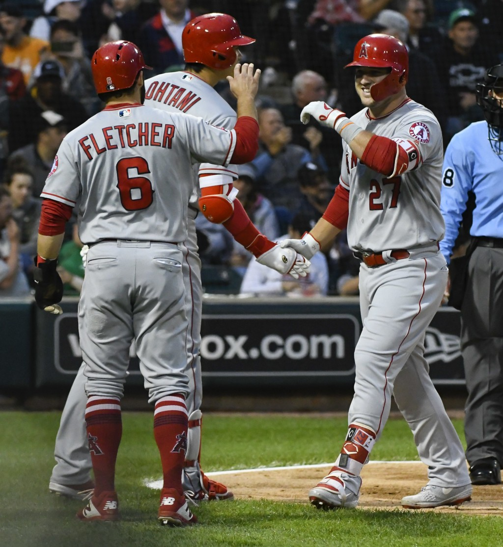 Los Angeles Angels' Mike Trout (27) high fives David Fletcher (6) and Shohei Ohtani, center, after Trout's three run home run during the third inning ...