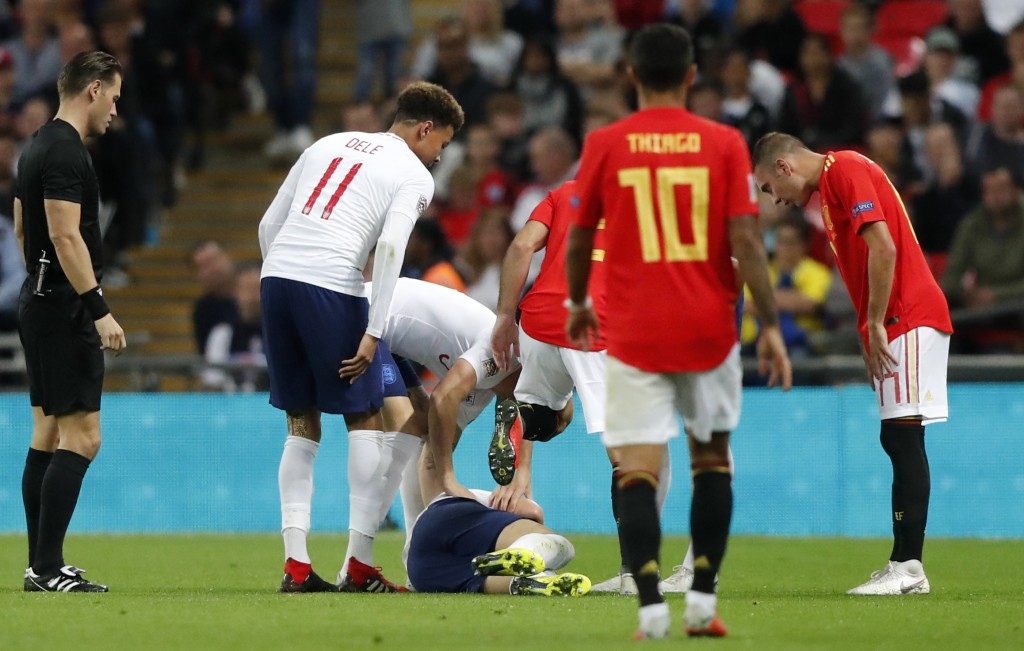 The players look at England's Luke Shaw on the ground after he injured himself during the UEFA Nations League soccer match between England and Spain a