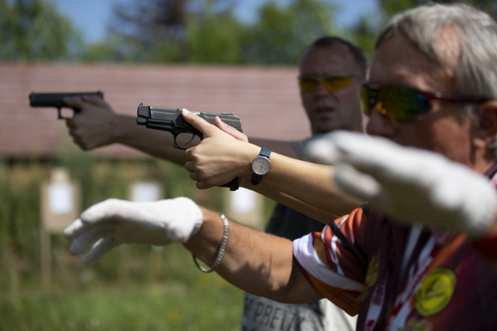 In this photo taken on Sunday, July 29, 2018, shooting instructor Boris Pashchenko demonstrates how to handle a gun at a shooting range in Moscow, Rus...