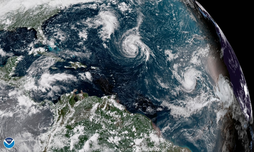 This enhanced satellite image made available by NOAA shows Tropical Storm Florence, center, in the Atlantic Ocean on Saturday, Sept. 8, 2018 at 2:45 p...