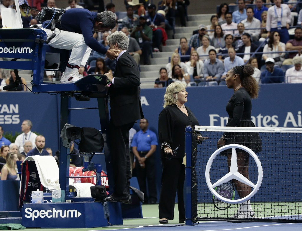 Chair umpire Carlos Ramos, left, talks with referee Brian Earley as Serena Williams talks with Donna Kelso during the women's final of the U.S. Open t