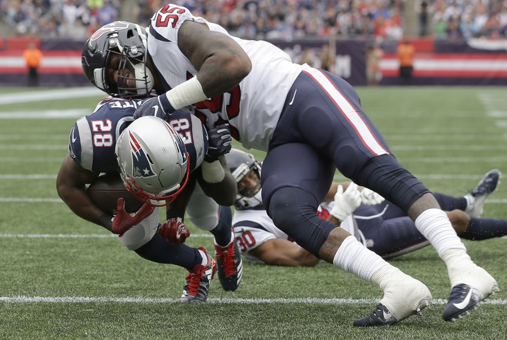New England Patriots running back James White (28) scores a touchdown past Houston Texans linebacker Benardrick McKinney (55) during the first half of