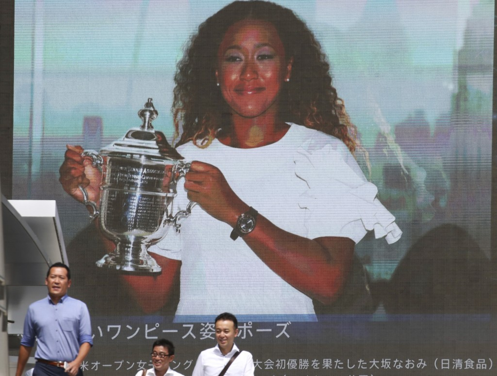 People walk by a huge screen showing US Open women's singles champion Naomi Osaka with her trophy, in Tokyo, Monday, Sept. 10, 2018. (AP Photo/Koji Sa