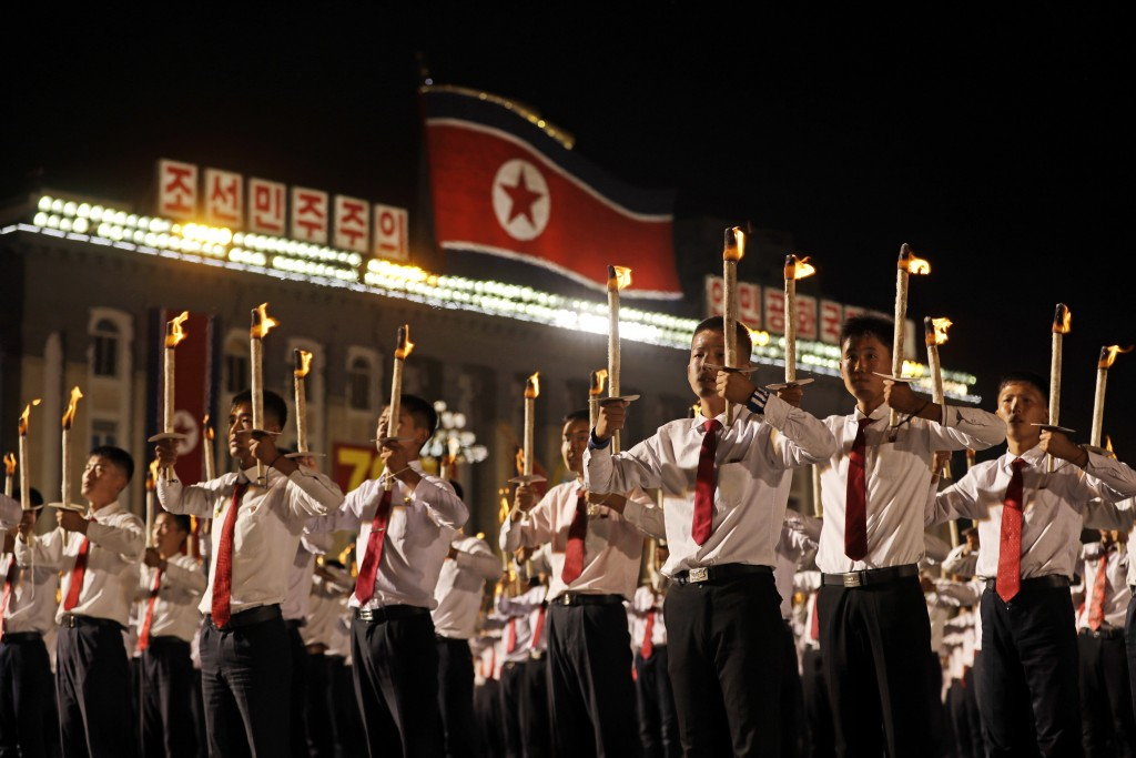 North Korean youths holding torches march during a torch light march at the Kim Il Sung Square in conjunction with the 70th anniversary of North Korea