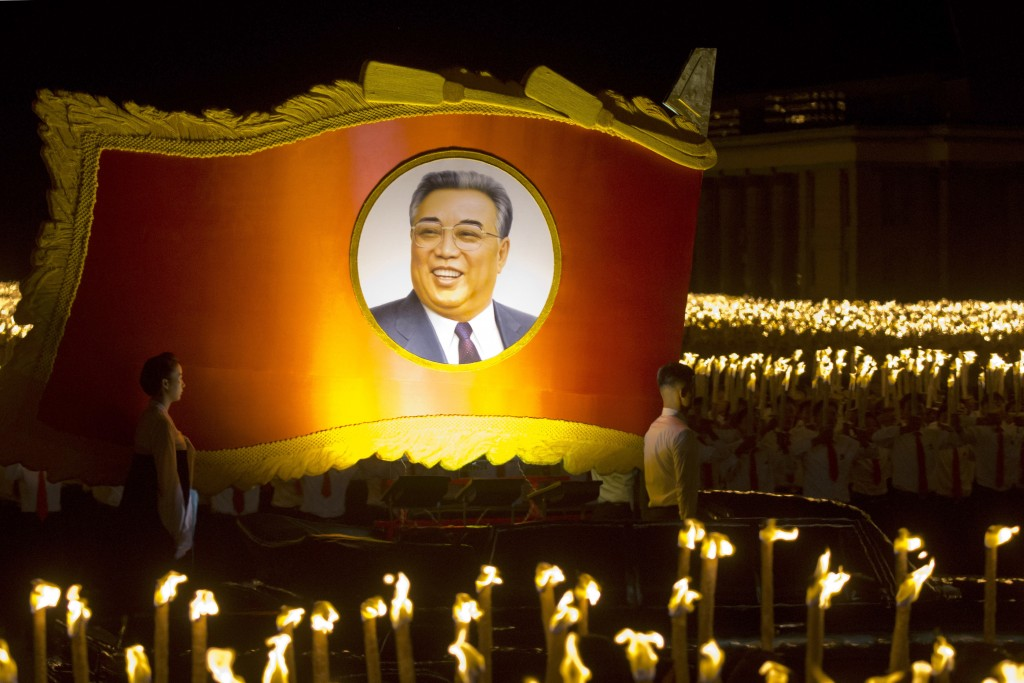 A float with a portrait of late North Korean leader Kim Il Sung passes by North Korean students taking part in a torch light march held in conjunction