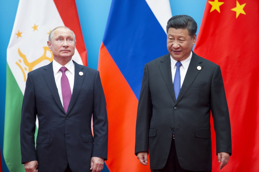 FILE - In this Sunday, June 10, 2018 file photo, Chinese President Xi Jinping, right, and Russian President Vladimir Putin pose for a photo at the Sha