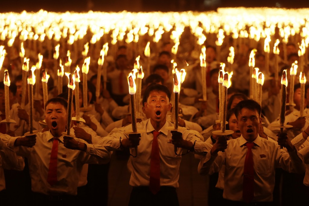 In this Monday, Sept. 10, 2018, file photo, North Korean youths holding torches march during the torch light march at the Kim Il Sung Square in conjun