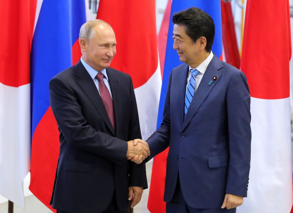 Japanese Prime Minister Shinzo Abe, right, and Russian President Vladimir Putin shake hands prior to their talks at the Eastern Economic Forum in Vlad