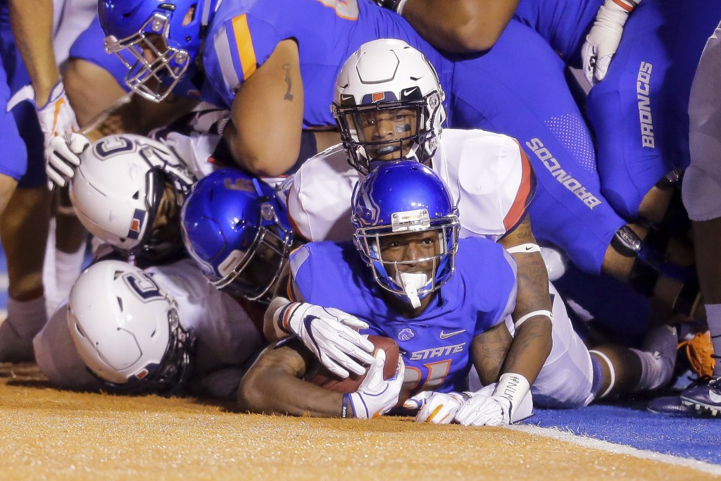 Boise State wide receiver Akilian Butler (81) looks up from under the pile of players he dragged in to the end zone for a touchdown against Connecticu