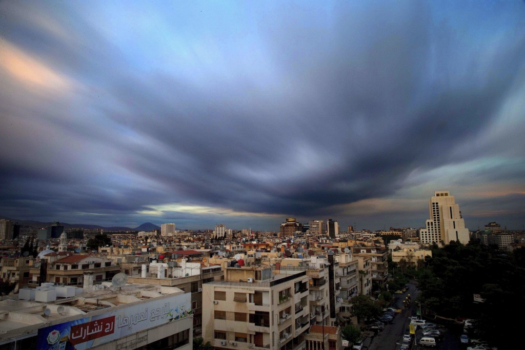FILE - In this April 12, 2016 file picture taken with a slow shutter speed, clouds hover over the capital city of Damascus, Syria. A new Syrian law em