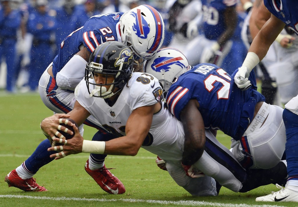Baltimore Ravens wide receiver Willie Snead (83) dives between Buffalo Bills defensive back Jordan Poyer (21) and defensive back Rafael Bush (20) for