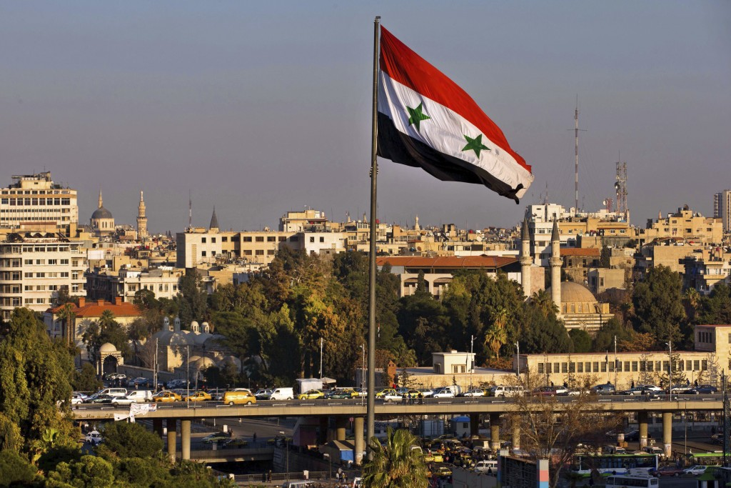 FILE - In this Feb. 28, 2016 file photo a Syrian national flag waves as vehicles move slowly on a bridge during rush hour, in Damascus, Syria. A new S