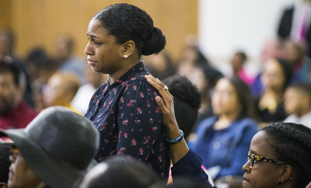 Cynthia Johnson, Botham Jean's girlfriend, stands up as she is comforted by another churchgoer during a prayer service for Jean at the Dallas West Chu